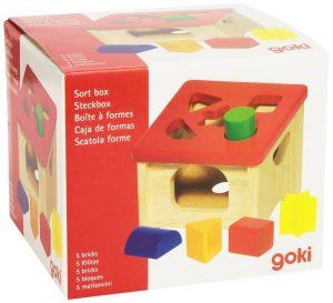 boîte à formes avec son dessus rouge vernis qui comprend cinq empreintes géométriques combinées à cinq pièces de la même forme.